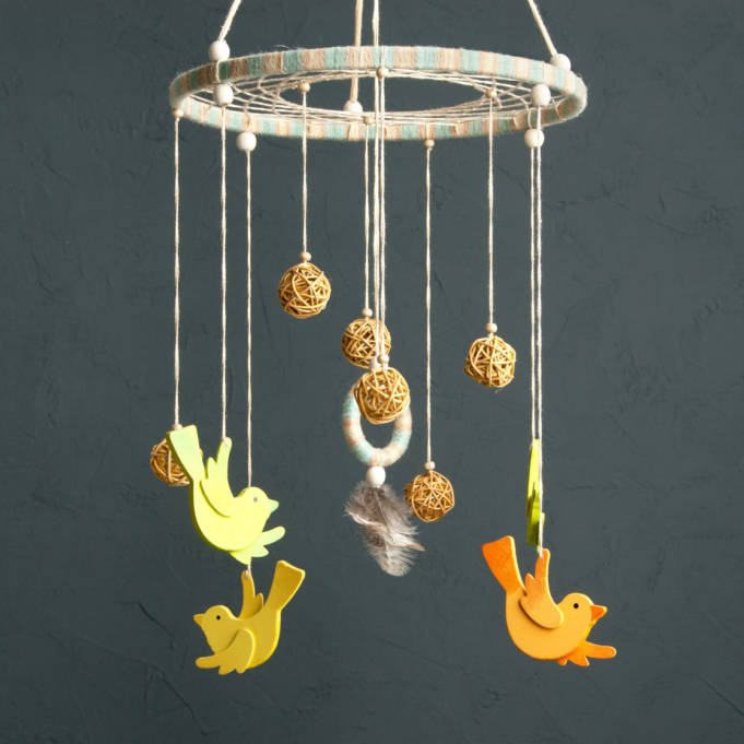 74421240 - handmade multicolor baby crib mobile with wooden birdies and rattan balls on gray background